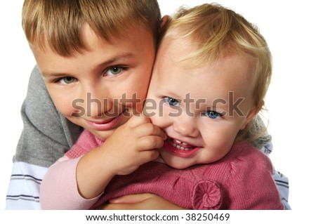 tween boy hugging his little sister; closeup faces - stock photo
