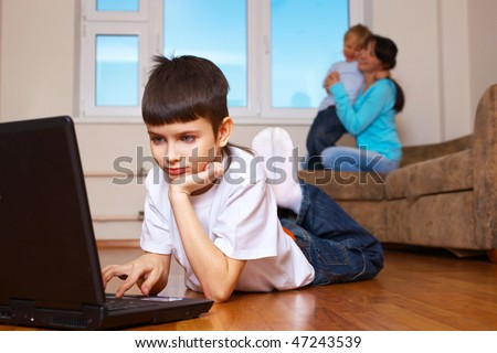 tween boy playing computer game while his mother with his brother playing - stock photo