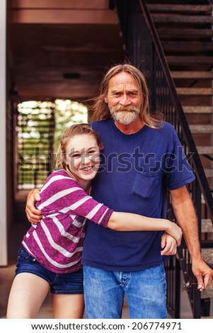 Tween girl hugging her grandfather -- image taken outdoors in Reno, Nevada, USA
