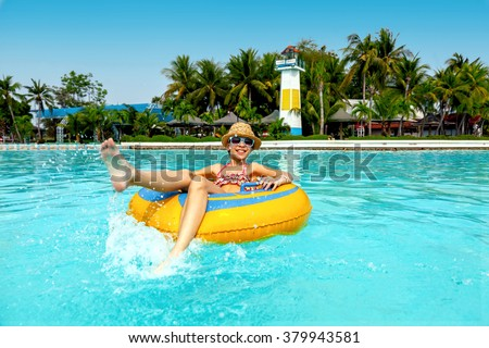 Tween girl relaxing on the inflatable ring in the water park in Thailand - stock photo