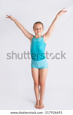 Tween girl standing on white backdrop doing a full body gymnastics salute. - stock photo