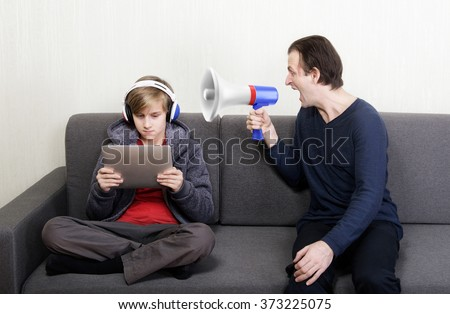 Tween son in headphones looks at the digital tablet display while his father yells at him through a megaphone
