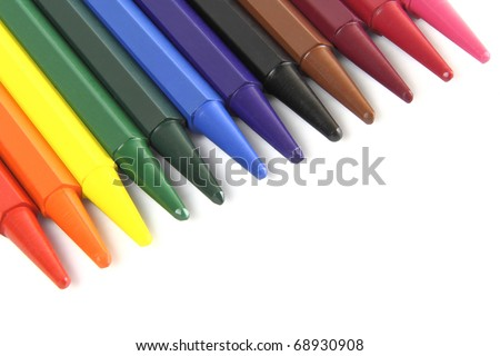 twelve color crayons lie over white background