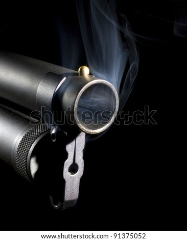 Twelve gauge shotgun that has smoke coming from its muzzle - stock photo