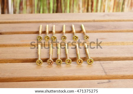 Twelve golden cross screws on wooden table