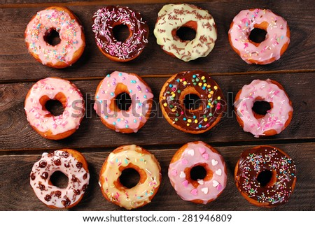 twelve homemade colorful donuts with chocolate and icing glaze on wooden background  - stock photo