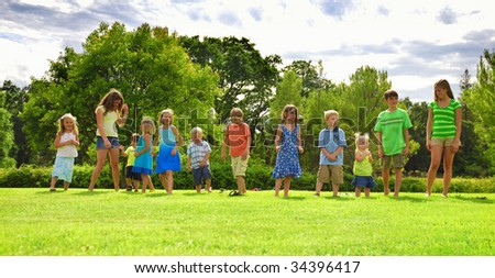 Twelve kids lined up on grass for a race - stock photo