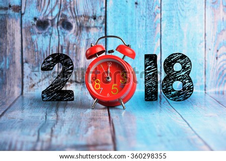 twelve o'clock on a round alarm clock and show year 2018 on wooden background. - stock photo