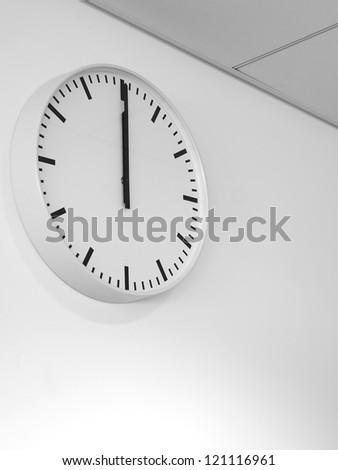Twelve o'clock on white wall watch - stock photo