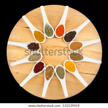 Twelve spices on black background - stock photo