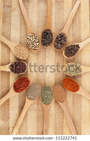 twelve spoons of spices like circle on cutting board - stock photo