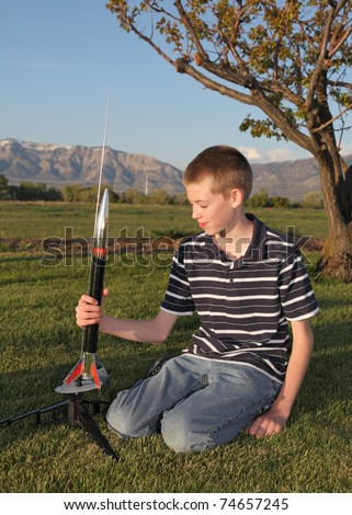 twelve year old boy playing with model rocket in countryside - stock photo
