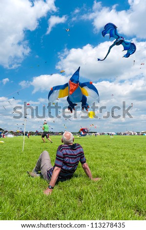 TWENTERAND, NETHERLANDS - JUNE 30: Man watches colorful kites at the 3rd international kite festival on june 30, 2012 in Twenterand, Netherlands. Most of the participants are from Germany and Belgium - stock photo