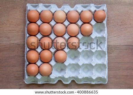 Twenty Eggs in paper tray on wooden background. - stock photo