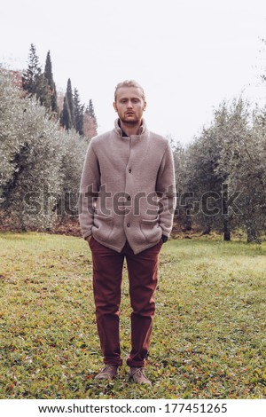 Twenty four year old man with blue eyes and blonde hair in a day of winter in a park  - stock photo