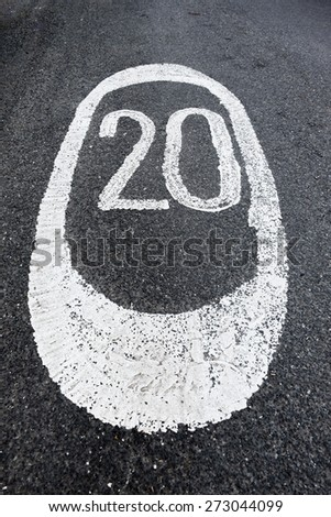 Twenty Miles per hour sign painted on the road UK - stock photo