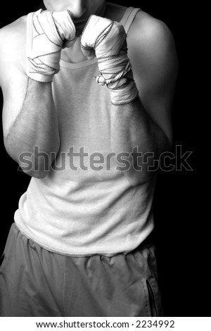Twenty seven years young man making boxer`s guard position. Wearing boxer`s home made wrapping bandages on his hands. Sleeveless t-shirt and grey sweatpants. Low light and black background.