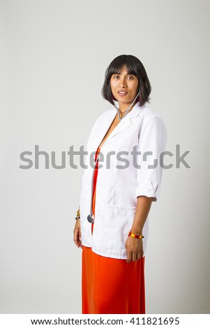 twenty something woman wearing a lab coat and stethoscope in her ears - stock photo