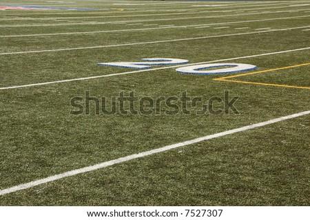 Twenty yard line of artificial turf football field. - stock photo