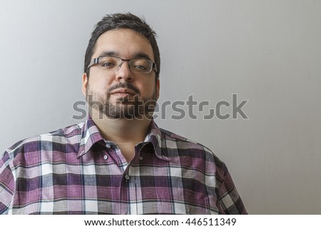 twenty year old man with serious expression against a white wall - stock photo