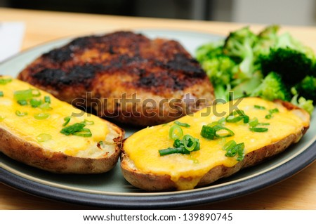 twice baked potato smothered with cheese and green onions with a breaded pork chop and vegetables - stock photo