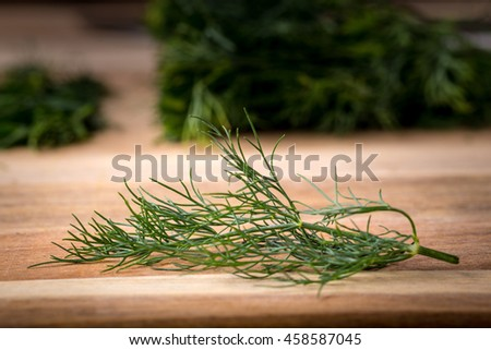 Twig of dill on a wooden board. Branch seasoning aromatic spice. - stock photo