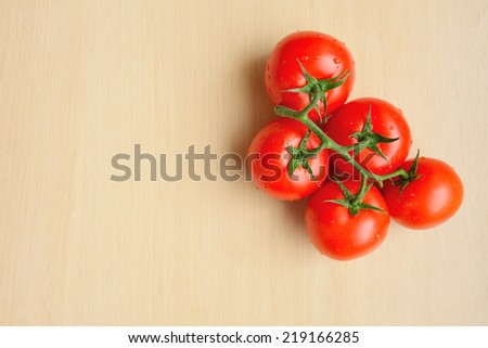 Twig of fresh tomatoes with water drops on wooden background