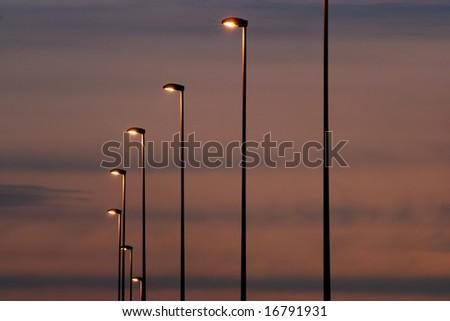 twilight city sky background with row of modern light masts - stock photo