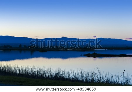 Twilight falls over the remote and vast Sacramento National Wildlife Refuge in the California Central Valley on a still evening - stock photo