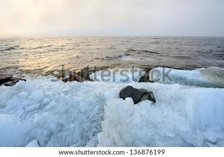Twilight foggy rubble ice Baltic seashore landscape with the hidden sun - stock photo