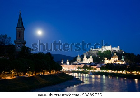 Twilight in Salzburg, view on church, river banks and fortress on the hill - stock photo