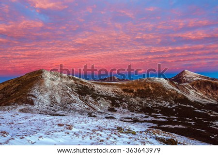 Twilight Mountain View Winter Landscape before Sunrise Forest and Snow on Hills and Summit red color clouds on Sky - stock photo