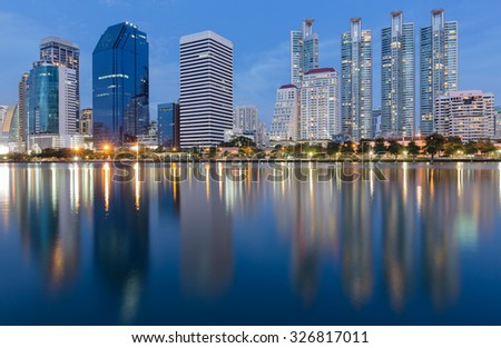 Twilight of Bangkok City downtown with water front reflection
