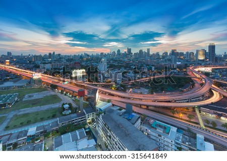 Twilight of city freeway intersection and business area on background, Bangkok Thailand - stock photo