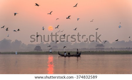 Twilight on the lake, a boat with holiday makers , warm tone - stock photo