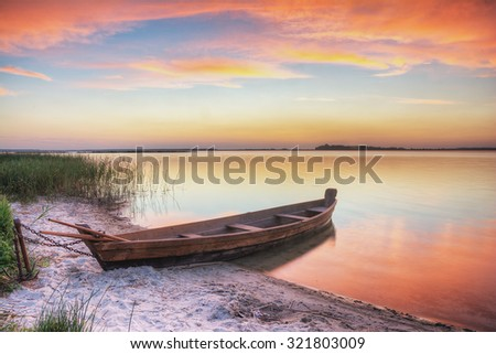 Twilight on the lake, fishing boats on the shore - stock photo