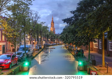Twilight scene in Delft along the Oosteinde canal with the Nieuwe Kerk (New Church) in the background. - stock photo