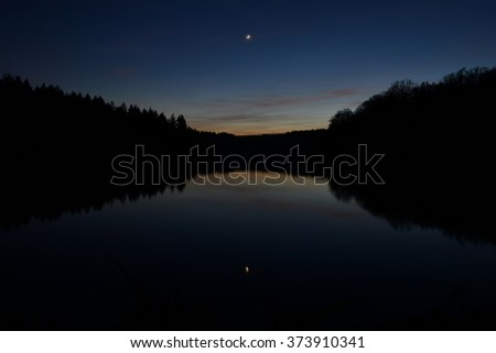 Twilight Sky Reflected over a Forest Lake - stock photo