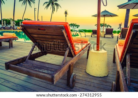 Twilight time Sunset umbrella deck chair pool - vintage filter effect
