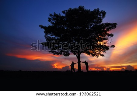 Twilight tree silhouettes with two young men.