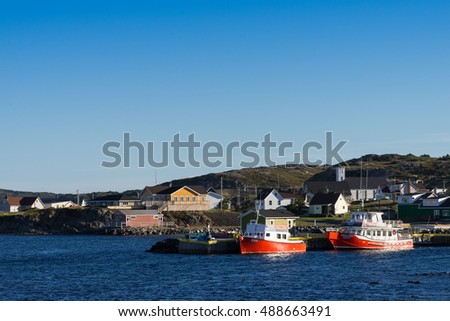 Twillingate, Newfoundland - September 13, 2016: Two red expedition boats for whale watching moored in early morning at the shore in Twillingate, Newfoundland