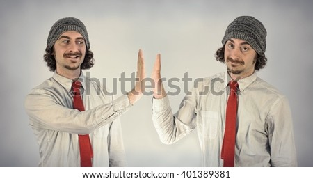 Twin adult men with beards high five eachother - stock photo
