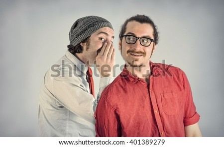 Twin adult men with beards tell secrets to eachother - stock photo