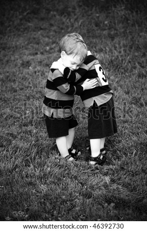 Twin baby boys hugging in rugby clothing