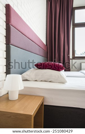 Twin bed in hotel with colorful headboard - stock photo