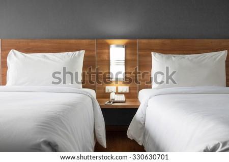 Twin bed with wood headboard. - stock photo