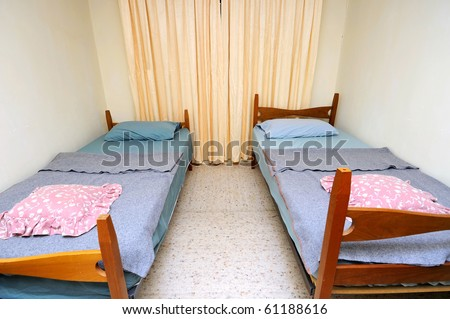Twin beds in simple motel room. Suitable for concepts such as budget travel, tourism, vacation and holiday, and relaxation. - stock photo