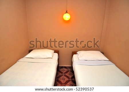 Twin beds neatly done up in a hotel room. Suitable for concepts such as travel, tourism, vacation and holiday. - stock photo