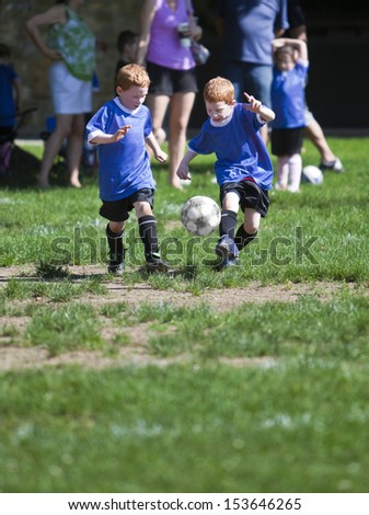 Twin boys playing soccer on a field - stock photo