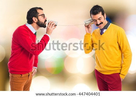 Twin brothers talking through a tin phone  on unfocused background - stock photo